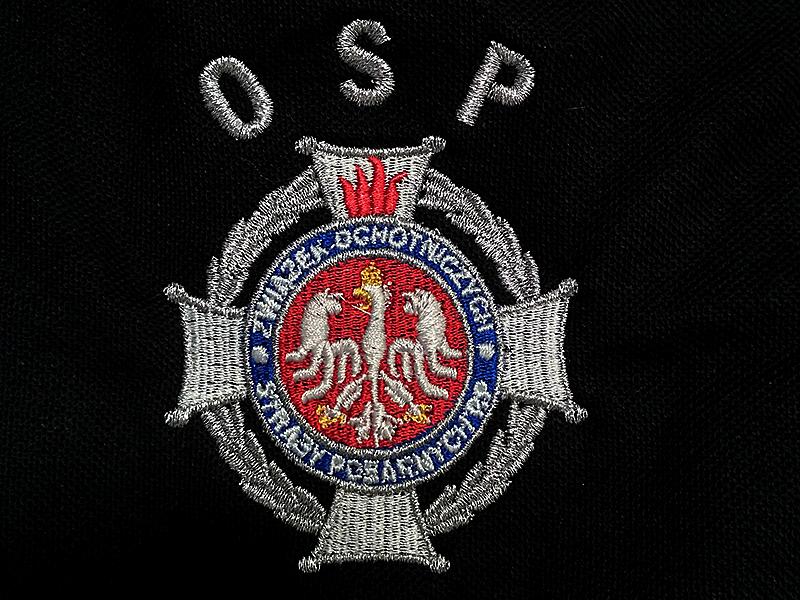 Haft na koszulkach polo dla Ochotniczej Straży Pożarnej. Haft logo OSP nicią metalizowaną.  Wyszywane logo Związku Ochotniczych Straży Pożarnych RP. Logotyp OSP wykonany srebrną nicią.